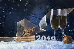 Due vetri di vino con champagne, l'orologio e gli ornamenti di Natale su un fondo nero con la riflessione fotografia stock