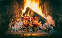 Due vetri di vino con Chardonnay sui precedenti di un camino bruciante immagine stock libera da diritti