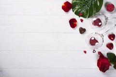 Due vetri di vino con i cuori rossi, i petali rosa ed i dolci del cioccolato Fotografie Stock