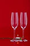 Due vetri di vino con rosa e candela sopra rosso Fotografie Stock