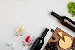 Due vetri di vino con vino rosso e bianco, bottiglie di vino rosso e di vino bianco, formaggio su fondo bianco Vista orizzontale Immagini Stock