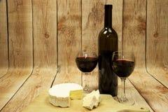 Due vetri di vino con vino rosso, la bottiglia di vino ed il formaggio su legno Fotografia Stock Libera da Diritti