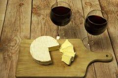 Due vetri di vino con vino rosso, la bottiglia di vino ed il formaggio su legno Immagine Stock