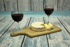 Due vetri di vino con vino rosso, la bottiglia di vino ed il formaggio su vint Fotografia Stock Libera da Diritti