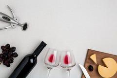 Due vetri di vino con vino rosso, la bottiglia di vino rosso ed il formaggio su fondo bianco Vista orizzontale dalla cima Immagini Stock