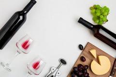 Due vetri di vino con vino rosso, la bottiglia di vino rosso ed il formaggio su fondo bianco Vista orizzontale dalla cima Fotografia Stock