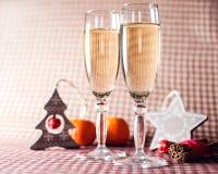 Due vetri di vino e decorazione di legno di Natale sui precedenti a quadretti rossi Immagine Stock