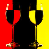 Due vetri di vino in lampadina sul colore rosso e sul yello Fotografie Stock Libere da Diritti