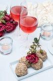 Due vetri di vino rosè, fiori freschi, dolci Fotografie Stock