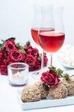 Due vetri di vino rosè, fiori freschi, dolci Fotografia Stock
