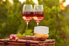 Due vetri di vino rosato con carne, l'uva, il pane ed il formaggio sulla t Immagine Stock