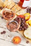 Due vetri di vino rosato e del bordo con i frutti, il pane ed il formaggio Immagini Stock