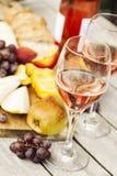 Due vetri di vino rosato e del bordo con i frutti, il pane ed il formaggio Fotografia Stock Libera da Diritti