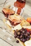 Due vetri di vino rosato e del bordo con i frutti, il pane ed il formaggio Immagini Stock Libere da Diritti