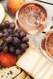 Due vetri di vino rosato e del bordo con i frutti, il pane ed il formaggio Fotografie Stock Libere da Diritti
