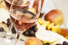 Due vetri di vino rosato e del bordo con i frutti, il pane ed il formaggio Fotografie Stock
