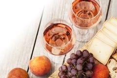 Due vetri di vino rosato e del bordo con i frutti, il pane ed il formaggio Fotografia Stock