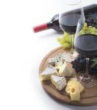 Due vetri di vino rosso, della bottiglia, del formaggio e dell'uva Fotografie Stock