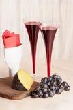 Due vetri di vino rosso, di formaggio e dell'uva immagine stock