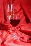 Due vetri di vino rosso e bianco su fondo rosso Immagine Stock