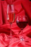 Due vetri di vino rosso e bianco su fondo rosso Fotografie Stock