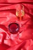 Due vetri di vino rosso e bianco su fondo rosso Immagine Stock Libera da Diritti