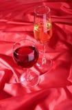 Due vetri di vino rosso e bianco su fondo rosso Fotografia Stock
