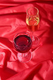 Due vetri di vino rosso e bianco su fondo rosso Fotografie Stock Libere da Diritti