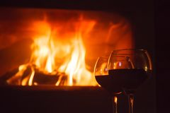 Due vetri di vino rosso in fonte del fuoco di ceppo Immagine Stock Libera da Diritti