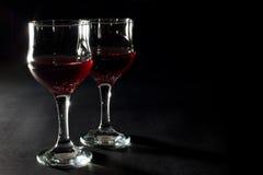 Due vetri di vino rosso isolati sul nero Fotografie Stock