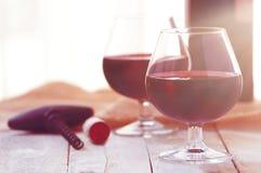 Due vetri di vino rosso su una tavola di legno bianca, luce di tramonto Fotografia Stock