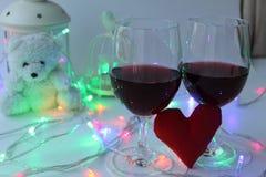 Due vetri di vino rosso, un cuore decorativo Un simbolo di amore Giorno del `s del biglietto di S immagine stock libera da diritti