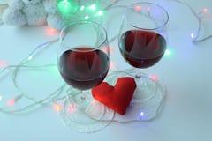 Due vetri di vino rosso, un cuore decorativo Un simbolo di amore Giorno del `s del biglietto di S fotografie stock