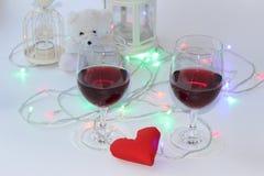 Due vetri di vino rosso, un cuore decorativo Un simbolo di amore Giorno del `s del biglietto di S fotografia stock