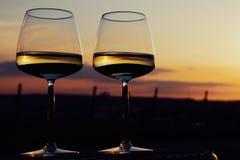 Due vetri di vino su un banco nel tramonto Fotografie Stock