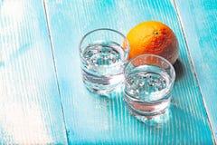 Due vetri di vodka su una tavola di legno dipinta in blu Fotografia Stock Libera da Diritti