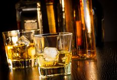 Due vetri di whiskey davanti alle bottiglie Fotografia Stock