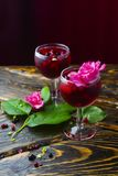 Due vetri pieni della bevanda rossa con le bacche, il ghiaccio e un flowe rosa Fotografia Stock