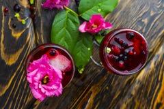 Due vetri pieni della bevanda rossa con le bacche, il ghiaccio e un flowe rosa Fotografia Stock Libera da Diritti