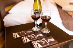 Due vetri sono riempiti di vino rosso Vicino ai bicchieri di vino stia una menzogne della bottiglia di vino e di alcun cioccolato Immagini Stock