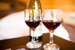 Due vetri sono riempiti di vino rosso Vicino ai bicchieri di vino stia una menzogne della bottiglia di vino e di alcun cioccolato Fotografia Stock
