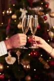 Due vetri tintinnanti del champagne delle mani sopra il backg vago del nuovo anno Immagine Stock