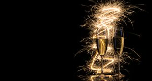 Due vetri trasparenti di champagne alle luci di Bengala immagini stock