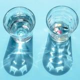 Due vetri trasparenti In un'acqua e nelle altre pillole colourful immagine stock