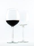Due vetri trasparenti - uno in pieno di vino rosso e l'altro è vuoto - su un fondo bianco Immagini Stock Libere da Diritti
