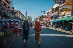 Due viaggiatori con zaino e sacco a pelo, camminanti giù la strada di Khao San, a Bangkok Immagine Stock