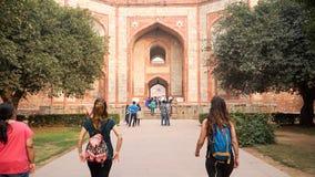 Due viaggiatori con zaino e sacco a pelo europei femminili che camminano verso il monumento indiano Immagine Stock Libera da Diritti