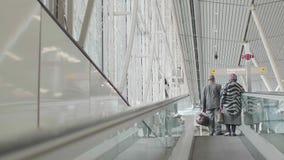 Due viaggiatori guidano un tappeto mobile nell'aeroporto di Schiphol video d archivio