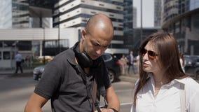 Due viaggiatori, un uomo e una donna, cambiano la batteria in una macchina fotografica di azione nel centro urbano video d archivio
