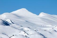 Due viandanti dello sci che camminano verso l'incrocio della sommità Raggi di sole e lampadina fotografie stock